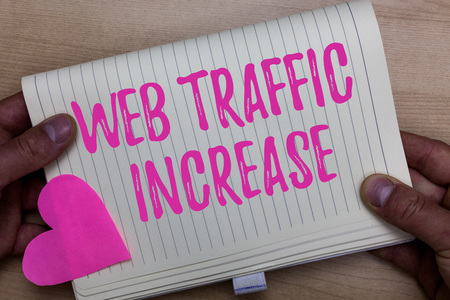 Writing note showing Web Traffic Increase. Business photo showcasing Expand Visitors to a Websitea number of Visits Man holding notebook paper heart Romantic ideas Wooden background