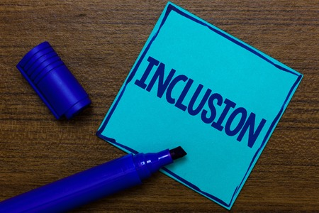 Writing note showing Inclusion. Business photo showcasing action state including of being included within group or structure Blue Paper Important reminder Communicate ideas Wooden background Stock Photo
