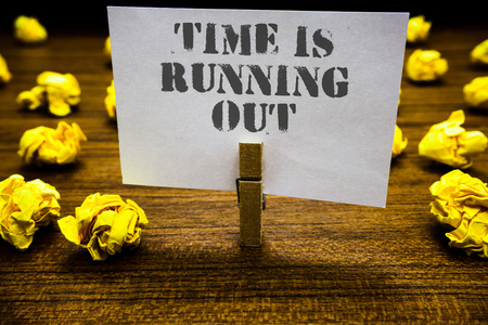 Text sign showing Time Is Running Out. Conceptual photo Deadline is approaching Urgency things cannot wait Paperclip grip white page with grey text woody floor laid blurry yellow lob Фото со стока