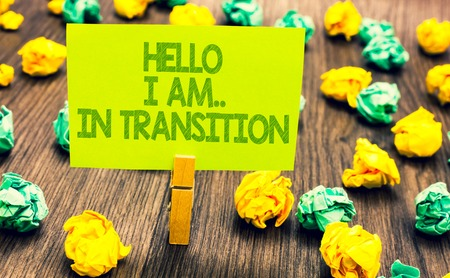 Handwriting text Hello I Am.. In Transition. Concept meaning Changing process Progressing planning new things Paperclip retain written words yellow paper paper lobs laid on wooden floor