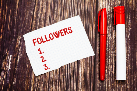 Handwriting text Followers. Concept meaning demonstrating who supports and admires particular demonstrating or ideas Blank Torn Index sized Graph Paper Two Pens for Writing on Wood Surface