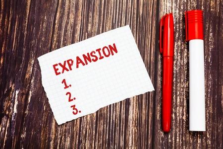 Erweiterung des Handschrifttextes. Begriff Sinne Aktion wird größer oder umfangreichere Vergrößerung von etwas leer zerrissen Index Größe Millimeterpapier zwei Stifte zum Schreiben auf Holzoberfläche