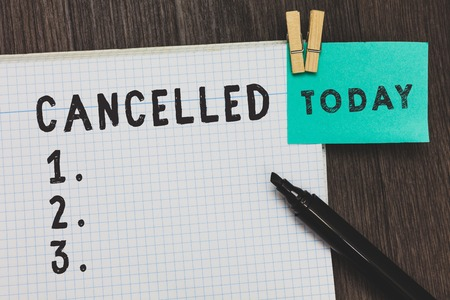 Writing note showing Cancelled. Business photo showcasing decide or announce that planned event will not take place Open notebook page pins holding reminder marker wooden background