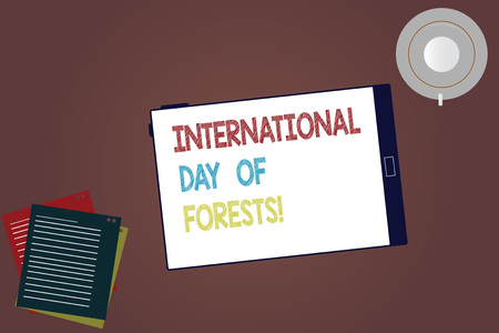 Word writing text International Day Of Forests. Business concept for Natural environment protection celebration Tablet Empty Screen Cup Saucer and Filler Sheets on Blank Color Background Stock Photo