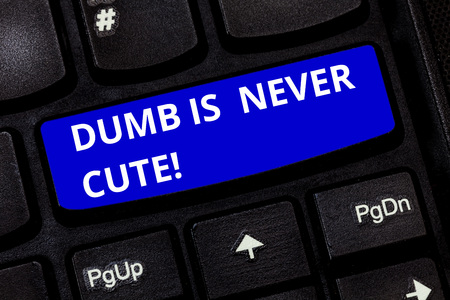 Text sign showing Dumb Is Never Cute. Conceptual photo To be stupid ignorant is never an attractive feature Keyboard key Intention to create computer message pressing keypad idea