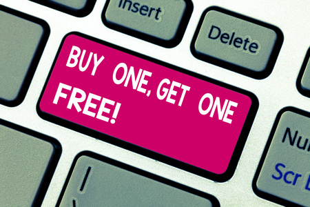 Text sign showing Buy One Get One Free. Conceptual photo Promotion discount special offering in gift card Keyboard key Intention to create computer message pressing keypad idea Фото со стока