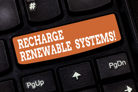Handwriting text writing Recharge Renewable Systems. Concept meaning Clean and sustainable energy and nonpolluting Keyboard key Intention to create computer message pressing keypad idea 免版税图像