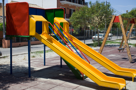 Screened Playground with Two Colorful Slides and Swing. Neighbourhood Public Park with Houses. Unsafe Recreational Activity Area because of the Flooring Reklamní fotografie