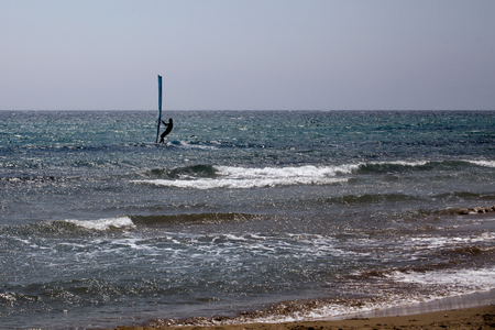 Wave Rider Windsurfing in the Ocean. Blue Water and Clear Sky. Sideview Far Shot of Surfer Balancing on Surfing Board with Sail. Outdoor Sport Adventure