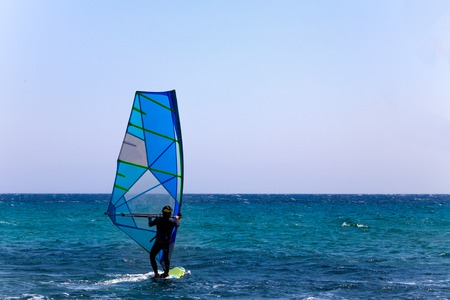 Rider in Wetsuit and Helmet Balancing on a Surfboard with Sail Mast and Bar. Clear Sky and Blue Wave. Surfer Trying out the Outdoor Water Sport Adventure
