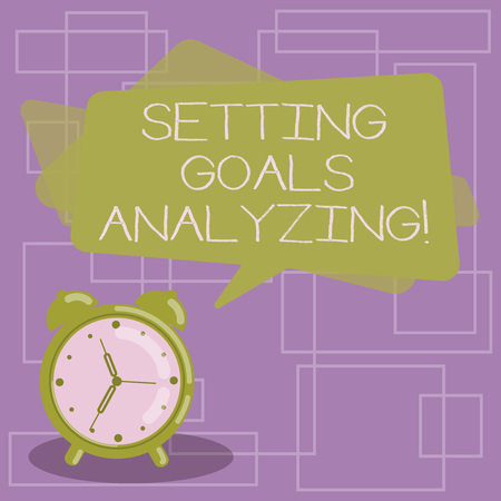 Text sign showing Setting Goals Analyzing. Conceptual photo Helped to be realistic about what can really achieve Blank Rectangular Color Speech Bubble Overlay and Analog Alarm Clock Фото со стока