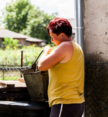 A view of a woman holding a metallic bucket looking deeply. The woman fetching water from the natural well. Typical household chore. Rural area scenario