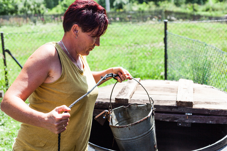 View of a hardworking mother holding a metal bucket with a string attached. The woman fetching potable drinking water from a natural well. Housewife daily activity. Countryside living scenario