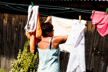 Back view of a woman hanging up clothes outside the house in one bright sunny day. Strings and clips are used in securing the garments from falling down. Urban living scenario Imagens