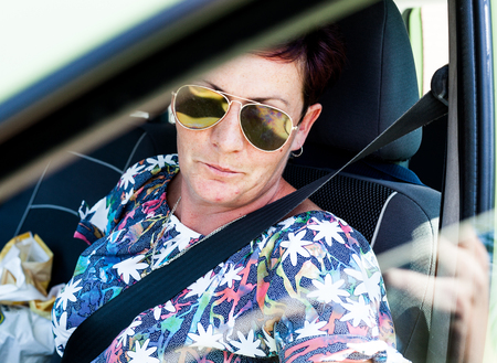 A middle aged woman driving a modern car. The lady driver wearing sunglasses to protect bright rays of the sun. Driving back from shopping items. Doing errands concept