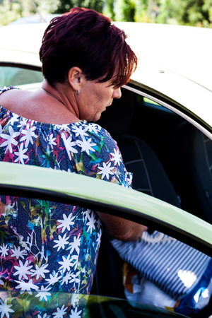 Back view of a woman putting grocery items inside the car. The sun rays striking bright on the color dyed hair of the lady driver. Housewife everyday routine activity. Doing errands idea