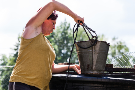 A view of hardworking woman holding a bucket of metal container. The housewife fetching water from a natural source. Typical daily household chore. Countryside living scenario Imagens