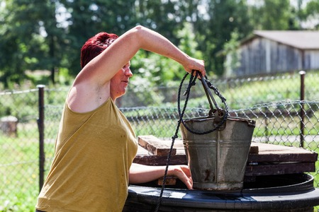 Side view of a woman pulling the bucket from well in one summer day. The lady getting the water in a natural source. Typical daily activity of a housewife. Countryside living scenario