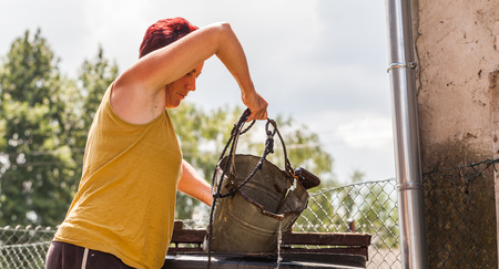 A woman working hard fetching water from the natural well. The middle aged mother pulling the metal container with a string.  Typical daily household chore. Countryside living scenario
