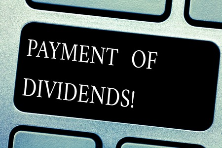 Handwriting text Payment Of Dividends. Concept meaning Distribution of profits by the company to shareholders Keyboard key Intention to create computer message pressing keypad idea