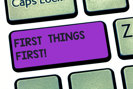 Handwriting text writing First Things First. Concept meaning important matters should dealt with before other things Keyboard key Intention to create computer message pressing keypad idea