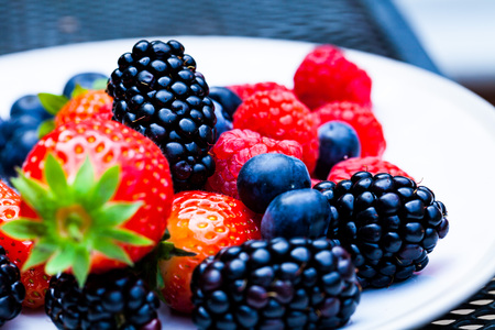 Raspberry blackberry and strawberries served on the plate. Nature and food concept image with fresh fruits on the plate Stockfoto