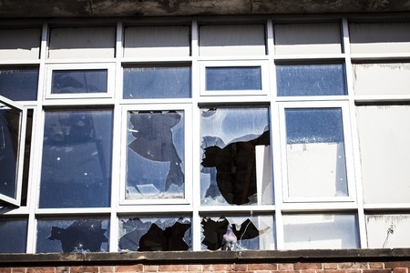 Smashed windows on the house. Broken glass on the wooden windoes. Old and demolished windows on the building