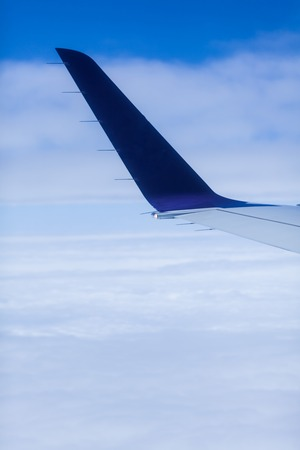 Tail of an airplane on a flight in the blue sky background. Copy space with aeroplane travel concept