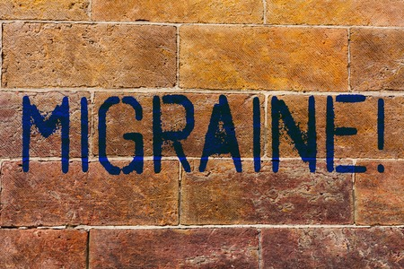 Conceptual hand writing showing Migraine. Concept meaning Recurrent headache in one side of head nausea and disturbed vision Brick Wall art like Graffiti motivational written on wall Foto de archivo