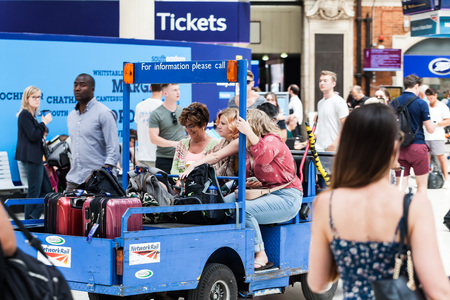 BIRMINGHAM, UK - March 2018 Baggage and People Trolley in One inside Train Station. Men and Women Walking on a Busy Day in London Victoria. Information ads and Boards Scattered Around