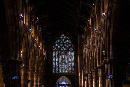 BIRMINGHAM, Großbritannien - März 2018 Glasmalerei, die die dunkle Endwand beleuchtet. Gewölbte Säulen auf beiden Seiten des Flurs. Künstlerische Handwerkskunst, eine Geschichte aus farbigen Scheiben zu erstellen