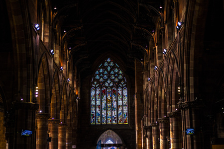 BIRMINGHAM, UK - March 2018 Stained Glass Illuminating the Dark End Wall. Arched Pillars on Both Sides of the Hallway. Artistic Craftmanship of Creating a Story out of Colored Pane