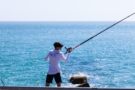 Brighton, UK - June 2018 Man with Cap Standing Ashore Holding Long Fishing Rod with Reel. Crystal Blue Wavy Water on Sunny Day. Water Sport Activity and Vacation Destination Ideas Sajtókép