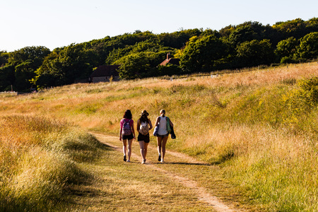 Brighton, UK - June 2018 Three Girls Walking on Greenfield Pathway on Sunny Day. People Passing through Grassy Footpath of Countryside Farm. Verdant Trees and Blue Sky as Backdrop