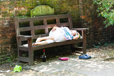 BIRMINGHAM, Reino Unido - marzo de 2018 anciana borracha durmiendo en un banco de madera. Botella de alcohol, bolsa y zapatos debajo del asiento. Alrededores sucios con hojas caídas esparcidas por el suelo