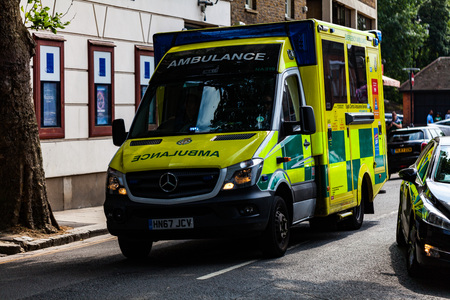 BIRMINGHAM, UK - March 2018 Ambulance Van Roving the Busy London Street. Yellow Vehicle Ready On Call for Emergency Assistance. Informative Messages Printed on Exterior of the Truck