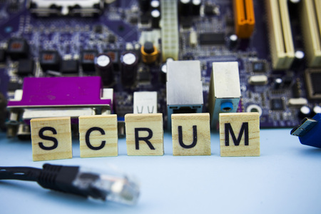 Word SCRUM on wooden blocks with information technology background. Computer mainboard background with scrum letters