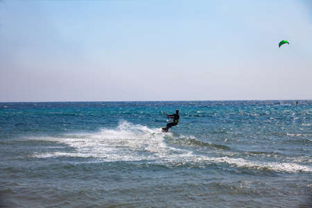 Water skiing with a board on a beautiful sunny day at the sea. Water sports concept image
