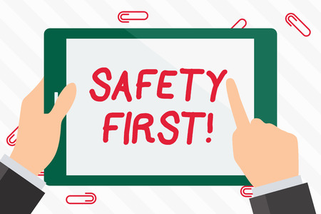 Text sign showing Safety First. Business photo showcasing best avoid any unnecessary risks and act so that you stay safe Hand Holding Pointing Touching Blank Rectangular Color Tablet White Screen Banque d'images