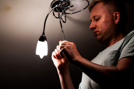 A middle-aged man changes the bulb on the ceiling. A man installs a new light bulb on the ceiling