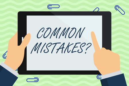 Writing note showing Common Mistakes question. Business concept for repeat act or judgement misguided or wrong Businessman Hand Holding and Pointing Colorful Tablet Screen
