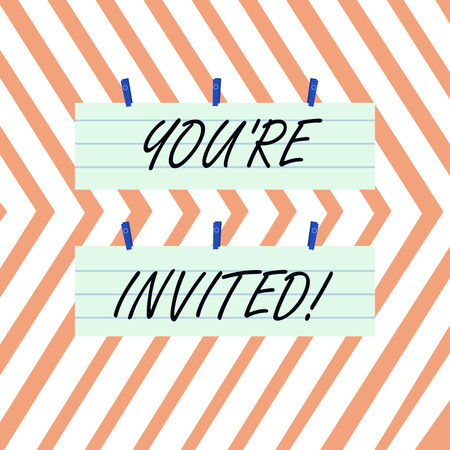 Writing note showing You Re Invited. Business concept for make a polite friendly request to someone go somewhere Strip Size Lined Paper Sheet Hanging Using Blue Clothespin Stock Photo