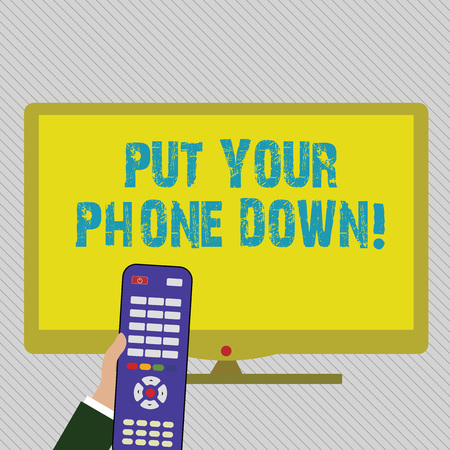 Text sign showing Put Your Phone Down. Business photo text end telephone connection saying goodbye caller Hand Holding Computer Remote Control infront of Blank Wide Color PC Screen