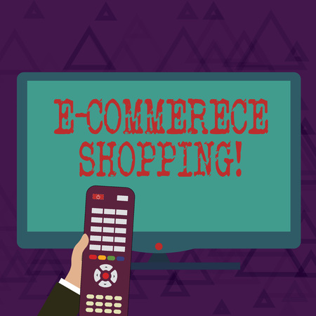 Writing note showing E Commerce Shopping. Business concept for directly buy goods or service from a seller over the web Hand Holding Remote Control infront of Wide Color PC Screen