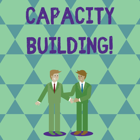 Handwriting text Capacity Building. Conceptual photo Strengthen the abilities of individuals Workforce planning Two Businessmen Standing, Smiling and Greeting each other by Handshaking Reklamní fotografie