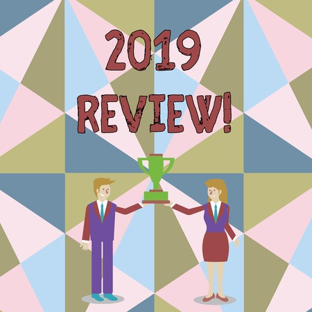 Word writing text 2019 Review. Business photo showcasing remembering past year events main actions or good shows Man and Woman in Business Suit Holding Together the Championship Trophy Cup