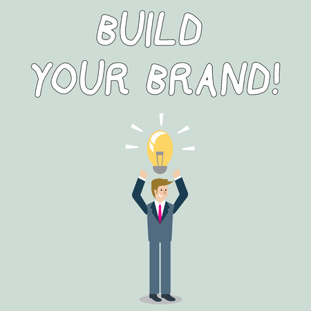 Word writing text Build Your Brand. Business photo showcasing creates or improves customers knowledge and opinions of product Businessman Standing Raising Arms Upward with Lighted Bulb Icon on his Head Reklamní fotografie - 122692538
