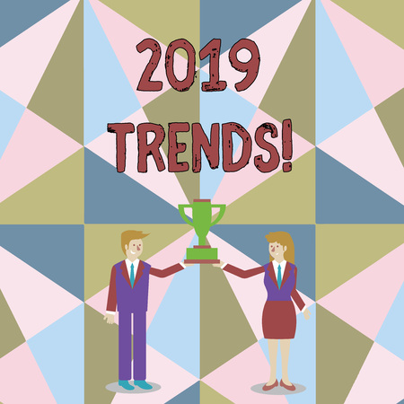 Word writing text 2019 Trends. Business photo showcasing general direction in which something is developing or changing Man and Woman in Business Suit Holding Together the Championship Trophy Cup