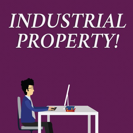 Writing note showing Industrial Property. Business concept for the intangible ownership of a trademark or patent Businessman Sitting on Chair Working on Computer and Books