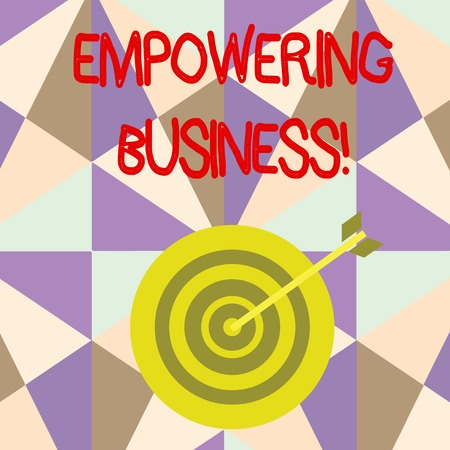Writing note showing Empowering Business. Business concept for creating an environment that fosters growth of business Dart Board in Concentric Style with Arrow Hitting the Center Bulls Eye Фото со стока